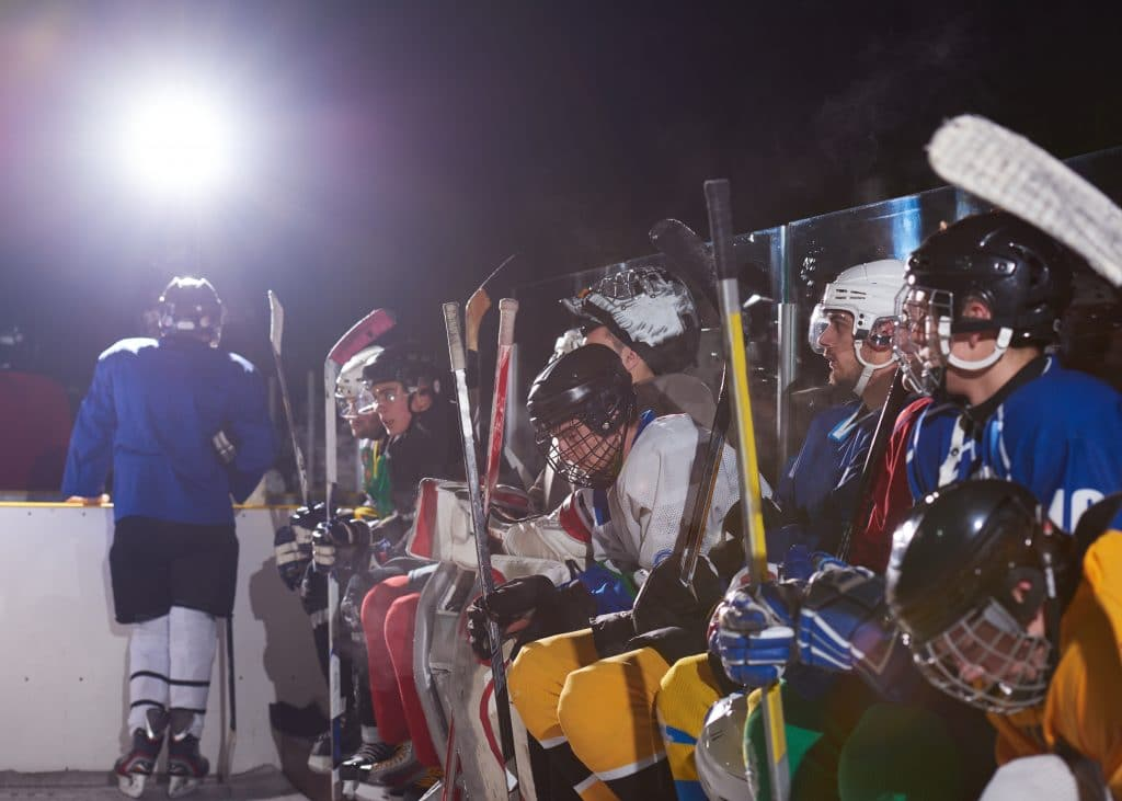hockey players in random colored gear lined up sitting on a bench holding their hockey sticks