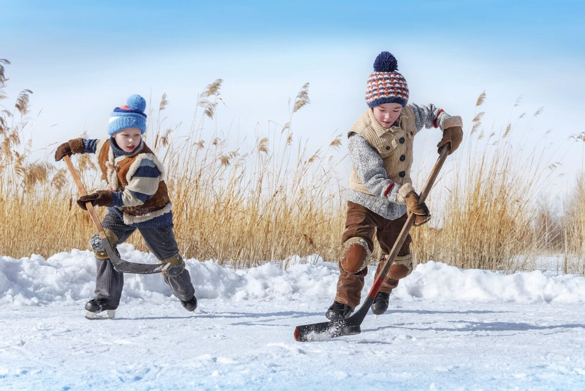 children play hockey on frozen pond outside