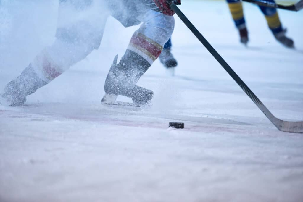ice hockey player in action with hockey pucks and sticks