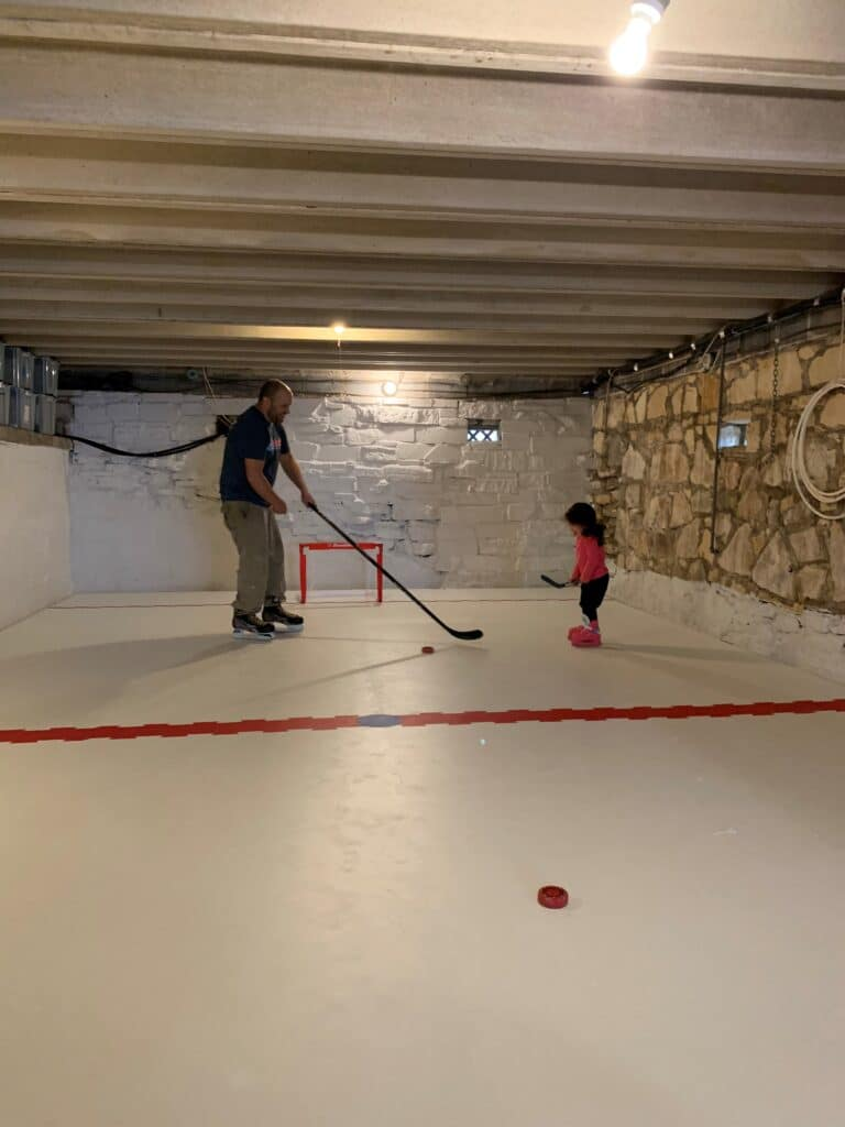 home indoor ice rink in basement with stone walls and a father and child playing hockey