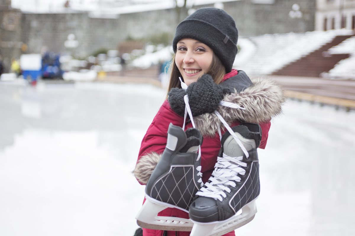 happy woman with ice skates outdoors