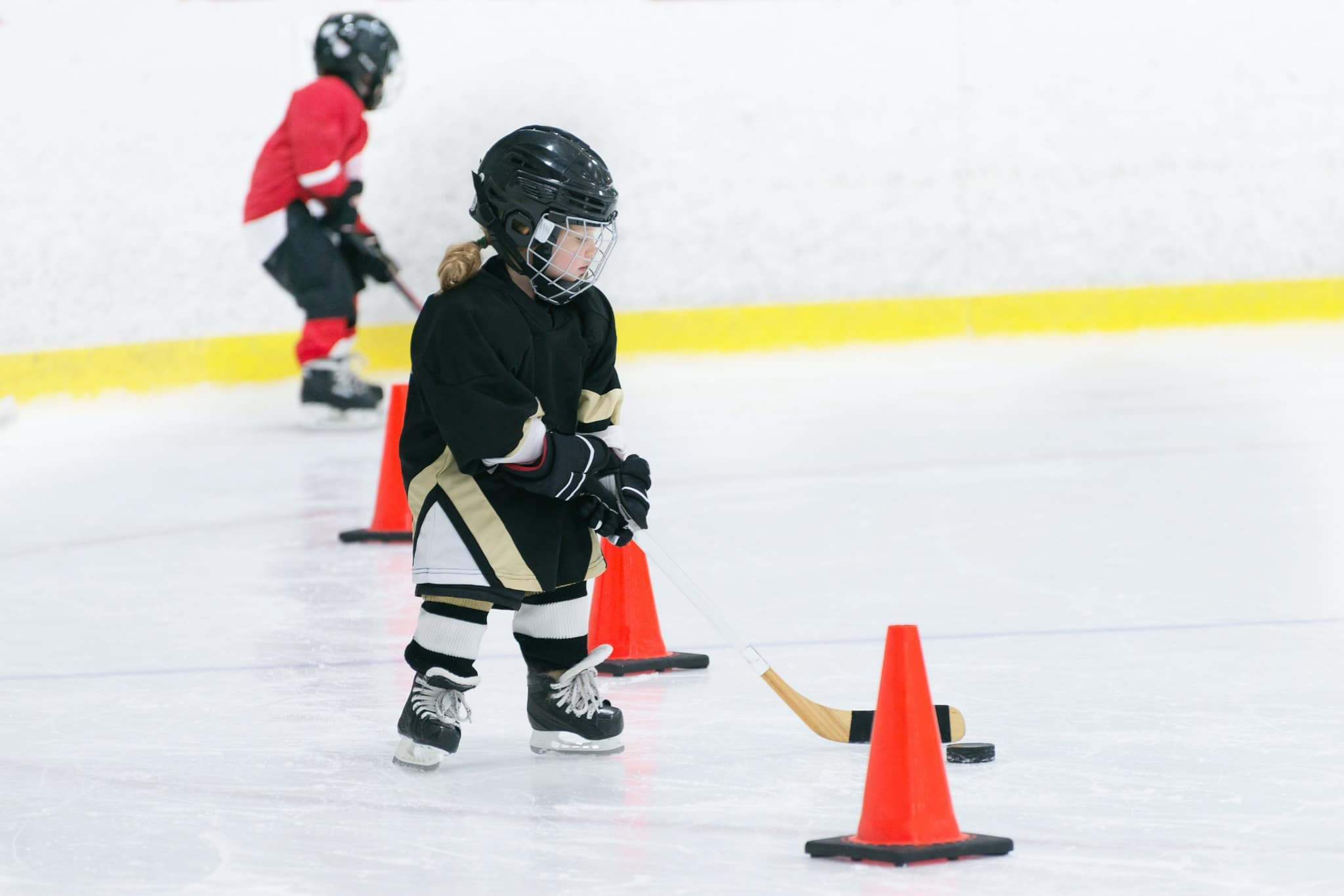 A girl playing hockey and doing the figure 8 drill