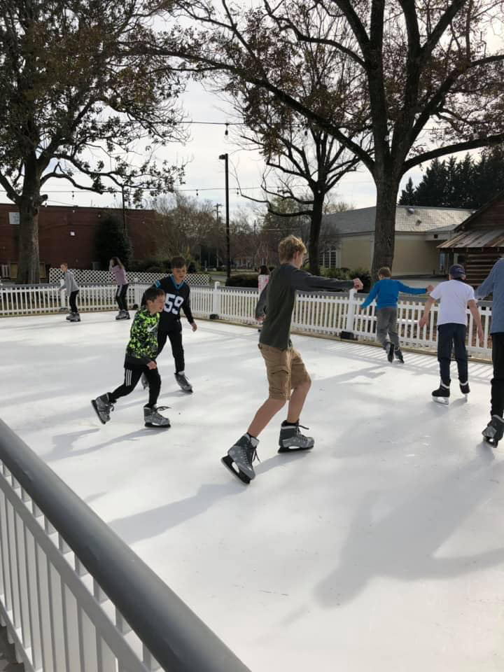 Kids skating outside in shorts and t-shirts on a synthetic ice rink built by KwikRink.
