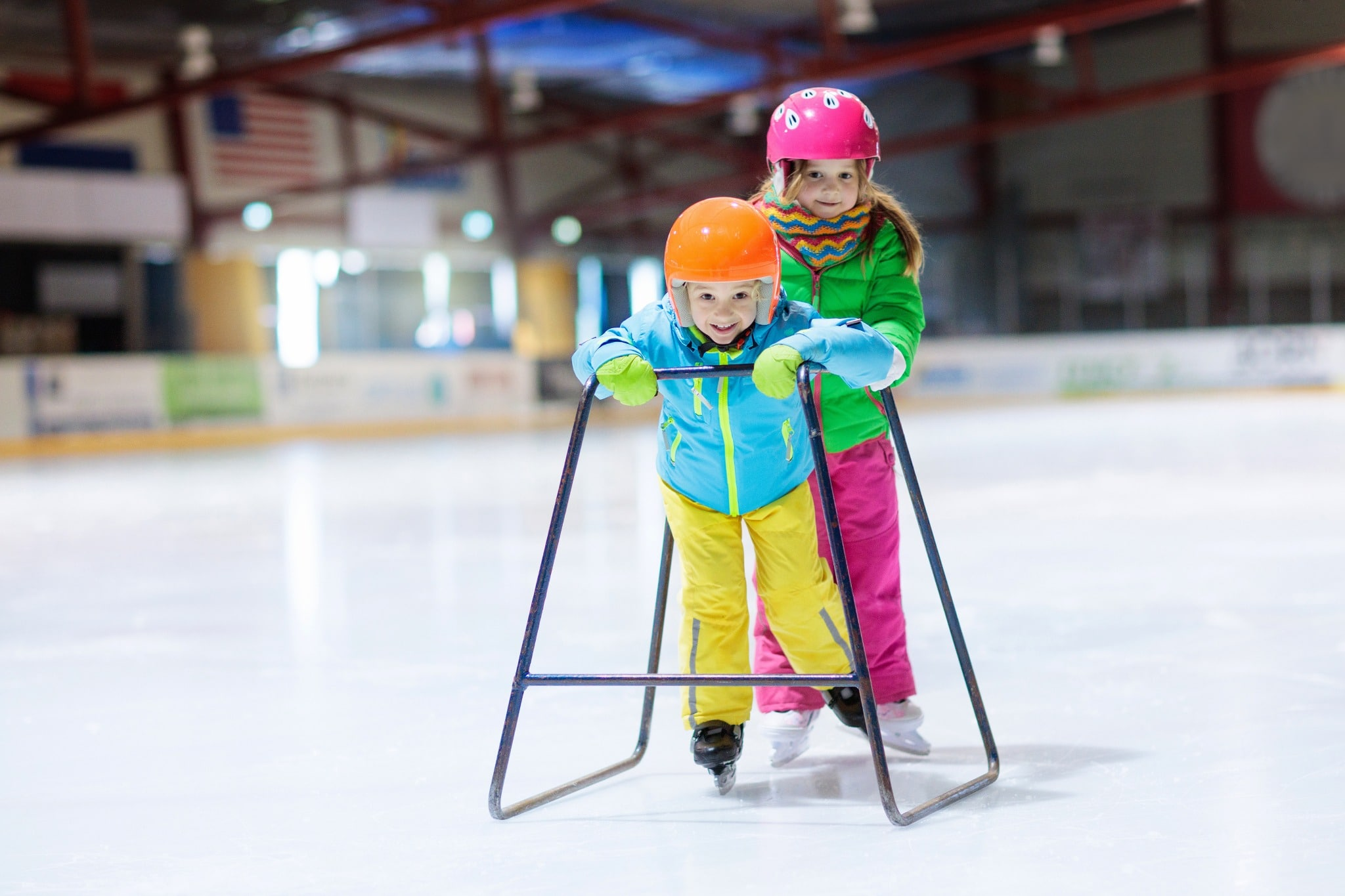 Two kids using a tool to help them learn how to ice skate on artificial ice